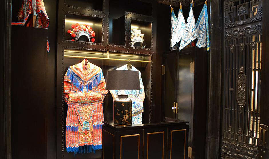 Tissus et déguisements d'opéras ornent les murs de la réception du Lili au Peninsula