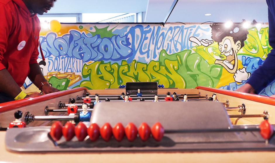 Etudiants jouant au babyfoot devant la création graffiti réalisée en direct
