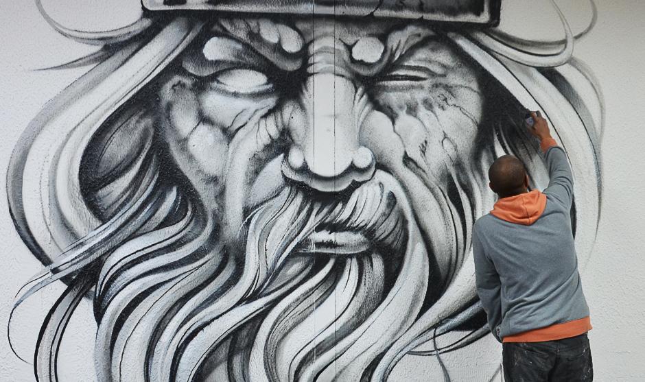 graffeur peignant un visage d'un homme barbu sur un mur