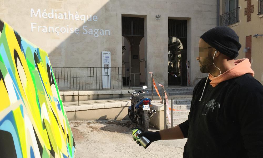 graffeur devant sa toile recouverte de couleurs