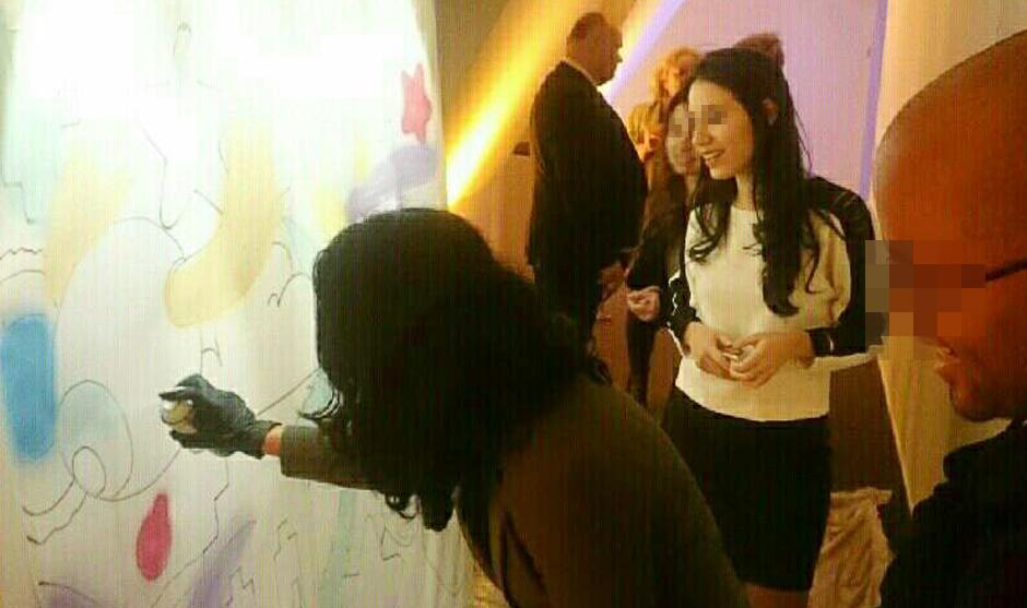 Jolie femme souriante devant une fresque graffiti