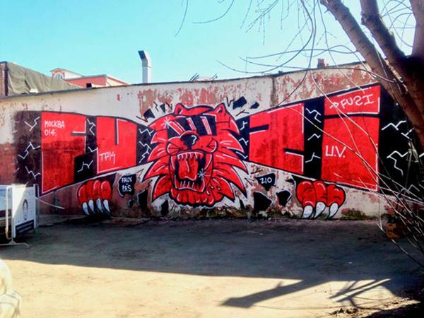 Lettrages et personnage rouge sur mur par le graffeur Fuzi