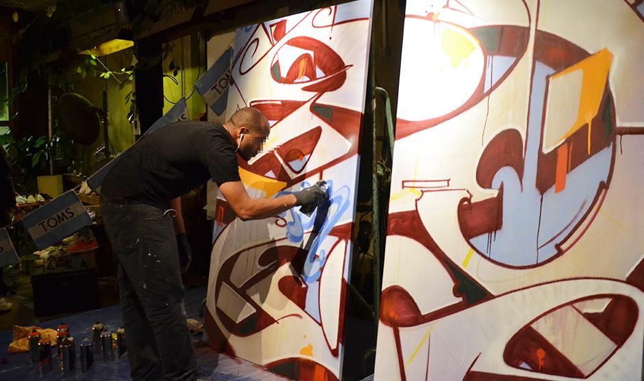 graffeur peignant un lettrage sur deux toile au cours de la soirée