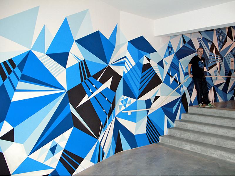 Street artiste Matt Moore devant fresque murale abstraite